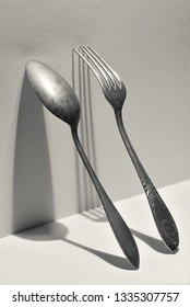 Concept of silver fork and spoon on wall