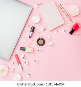 Concept with silver laptop, notebook, cosmetics and flowers on pink background. Top view. Flat lay.