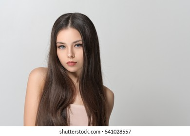 Concept skin care. Beautiful woman with bare shoulders has a clean well-groomed skin and long straight hair. Close-up portrait against a light gray background.