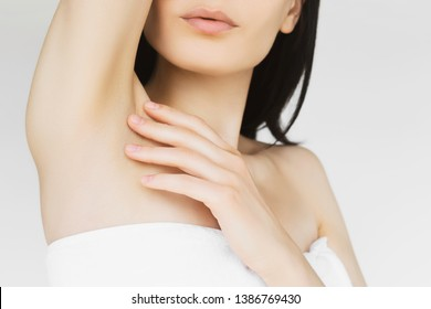 concept of skin care, cosmetology and hair removal. a woman in a white towel cares for the skin after epilation and sugaring, touches the skin on the armpits