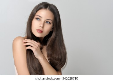Concept skin care and health. Beautiful woman with bare shoulders has a clean well-groomed skin and long straight hair. Close-up portrait against a light gray background.