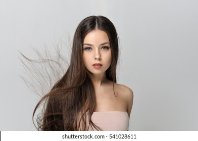 Concept skin care for women. Beautiful woman with bare shoulders has a clean well-groomed skin and long straight hair. Close-up portrait against a light gray background.