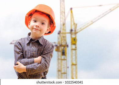 Concept, small boy in a helmet, looking at construction site with cranes