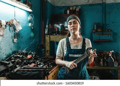 The concept of small business, feminism and women's equality. A young woman in overalls poses with a large wrench in her hands