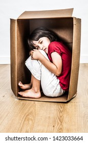 concept of small curled up sleeping child hunched in a tiny cardboard box, seeking for comfort, refuge from bullying, disrespect or violence from black education
