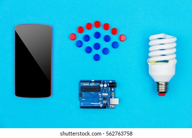 """Concept """"smart house"""". Top view of smartphone, microchips, microcontroller and led bulb on blue background with wifi symbol from colorful  hardware buttons"""