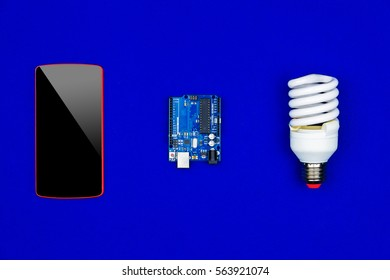 """Concept """"smart house"""". Top view of smartphone, microchips, microcontroller and led bulb on blue background"""