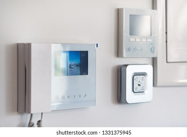 Concept of smart modern luxury wealthy home. On white wall home security alarm and video intercom with street view talkback or doorphone voice communications system close up, no people