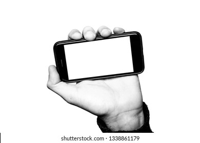 Concept of smartphone addiction or social network addiction. Hand holding a smartphone. The Display has a copy-space. The subject is black and white with a white background. Contemporary art collage.