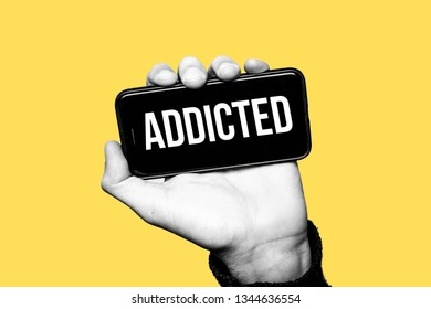 Concept of smartphone addiction or social network addiction. Hand holding a smartphone. Label ADDICTED in the screen. The subject is black and white with a yellow background. Contemporary art collage.