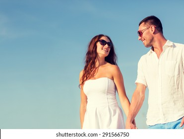 concept - smiling couple wearing sunglasses walking outdoors