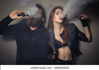 Concept of smoking in public places is steam and smoke. There are clubs of steam. Close-up of man and girl smoking electronic cigarettes vape-mod and drip. Couple vaping. Vape addiction concept.