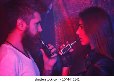 Concept of smoking in public places is steam and smoke. Bearded man and girl posing on camera and smoking an electronic cigarette. They release smoke in a nightclub. They hold boxmodes in their hands.