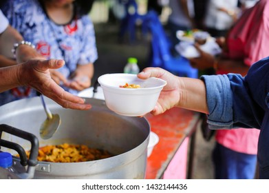 The concept of social sharing : Poor people receiving food from donations : Homeless people are helped with food relief, famine relief : volunteers giving food to poor people in desperate need
