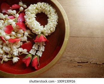 Concept for Songkran festival with Thai traditional handmade jasmine garland with rose petals and jasmine on kind of wooden utensil in northern Thailand, wooden background with sunlight.
