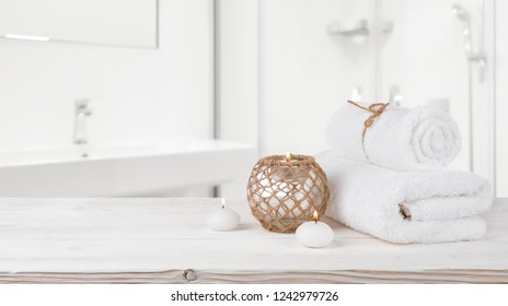 Concept of spa treatment on wooden table and blurred bathroom