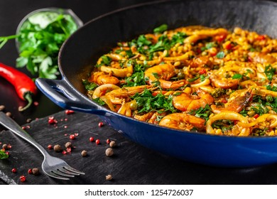 The concept of Spanish cuisine. Paella with seafood, shrimps, squid and greens, cooked in a wok pan on the street. street food.