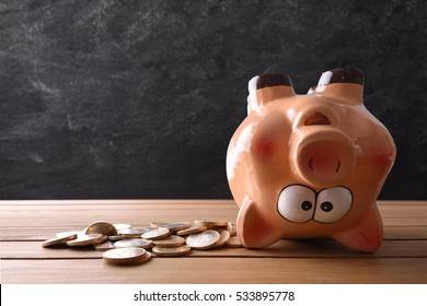 Concept of spending the savings with piggy bank upside down and blackboard background. Horizontal composition. Front view.