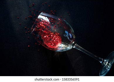 concept spilled red wine. end of the party. a glass of wine lying on a table in it red stars symbolizing spilled wine