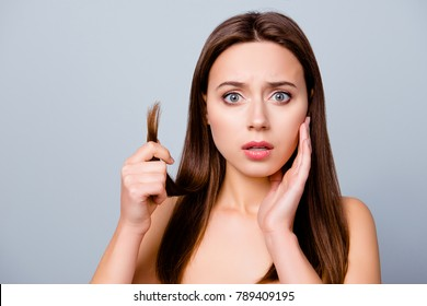 Concept of split ends. Close up portrait of frustrated unhappy sad woman showing her damaged hair, isolated on grey background, copy space