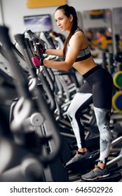 Concept of sport and healthy lifestyle. Strong young beautiful woman is engaged in a gym on an ellipsoid