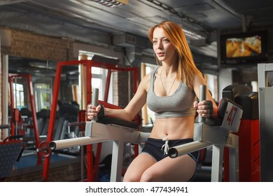 Concept: sport, healthy lifestyle. Young strong girl do leg lift for abs in gym