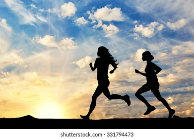 Concept of sport. Silhouette of two girls running competition at sunset