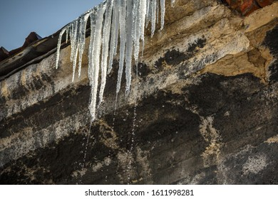 The concept of spring on earth. The warming after the winter. Melting icicles on the roofs of houses.