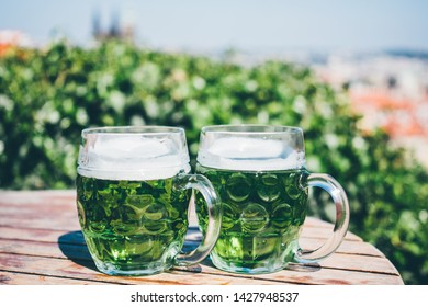Concept of St. Patrick's day with two glass of green beer at the panoramic cafe.