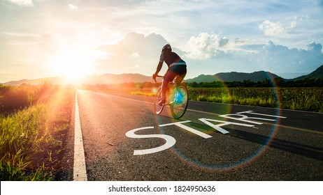 Concept of start straight and beginning for cooperation.Blurry Man ride on bike and word start written on the road at sunset add lens flare.Concept of challenge or career path,business strategy.