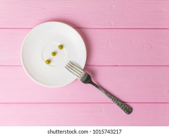 The concept of starvation, bulimia. A few peas on a white plate and a fork.