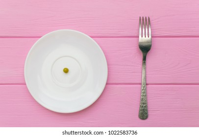 The concept of starvation, bulimia. Pea on a white plate and fork.