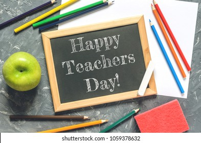 """a concept with stationery supplies for the teacher's day, a top view with the inscription """"Happy Teacher's Day"""""""