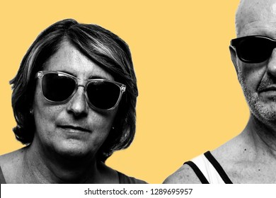 """Concept of """"Still rocking"""". Two people an old woman and an old man wearing sunglasses in black and white. The background is yellow, Getting older with rock and roll"""