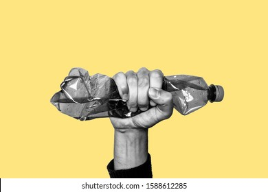 Concept of stop plastic pollution, global warming, recycling plastic, plastic free. Hand tightly squeezes an empty plastic bottle in a sign of protest. Yellow background with a black and white subject