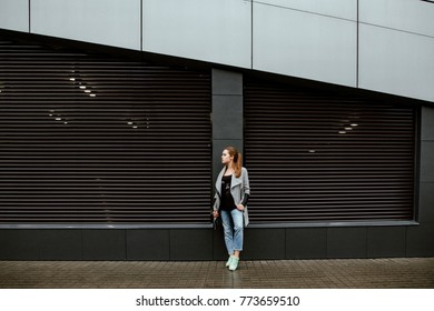 Concept of street fashion. An autumn portrait of the nice young smiling girl against the background of an impressive gray wall. Beautiful model in the city in a gray coat, blue jeans and a warm color