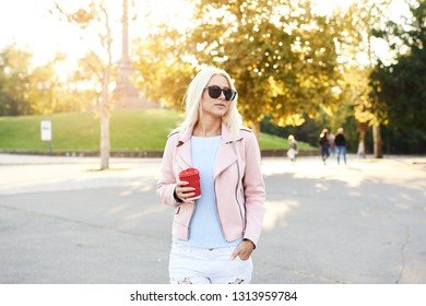 The concept of street fashion. young stylish girl student walking in the sunny park and holds a cup of coffee to go. portrait of smiling blond girl in sunglasses