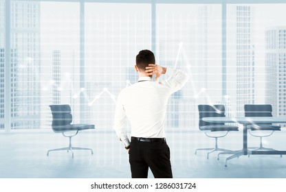 Concept of stressed businessman looking on chart going down in modern office