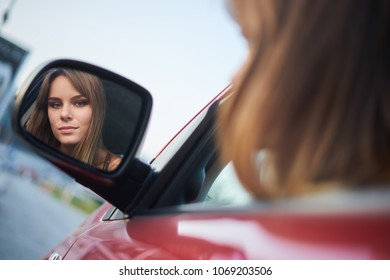 Concept: strong independent young woman in car. Beautiful serious girl sit behind the wheel at twilight looking in a mirror.