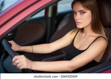 Concept: strong independent young woman in car. Beautiful serious girl sit behind the wheel at twilight. Outside look.