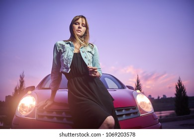 Concept: strong independent young woman with car. Beautiful serious girl fashionably stand near vehicle at twilight pink sunset. Lights are on