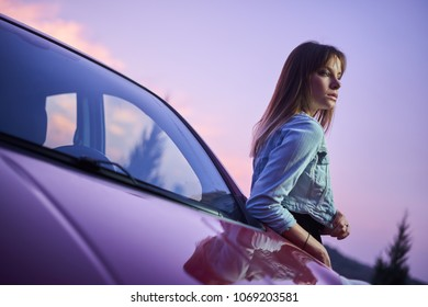 Concept: strong independent young woman with car. Beautiful serious girl fashionably stand near vehicle at twilight pink sunset.