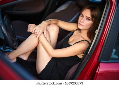 Concept: strong independent young woman in car. Beautiful serious girl sit behind the wheel in a sensual pose at twilight with open door and legs up.