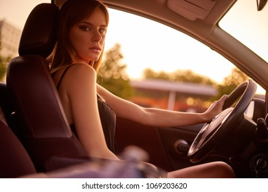 Concept: strong independent young woman in car. Beautiful serious girl sit behind the wheel at twilight. Inside look.