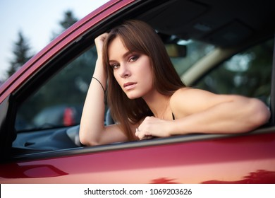 Concept: strong independent young woman in car. Beautiful serious girl sit behind the wheel at twilight looking through the window.