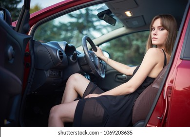 Concept: strong independent young woman in car. Beautiful serious girl sit behind the wheel at twilight with open door and one leg outside.