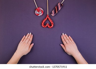 Concept of stylish french manicure, female manicure and lollypops,  striped lollypop looks like an ice-cream, round swirled and hart shaped  on a stick on violet background.