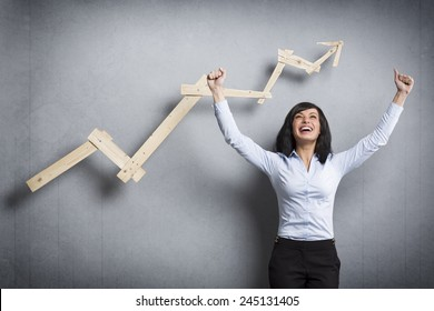Concept: Success in business or career. Enthusiastic businesswoman with raised arms cheering in front of positive business graph, isolated on grey background.
