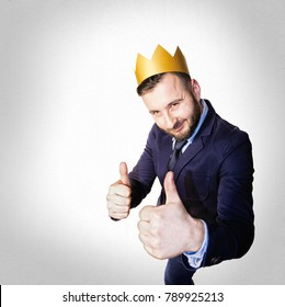 The concept of success. Portrait of a bearded man with a golden crown on his head on a light background.