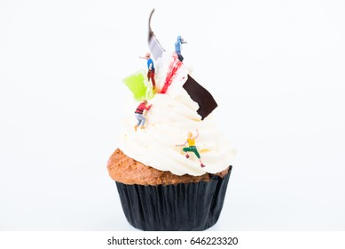 Concept of sugar high or sugar rush with miniature people going up the frosting of cupcake
